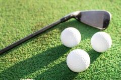 Drei Weißgoldbälle und ein Golfclub auf einer grünen künstlichen Rasenfläche stockfotografie