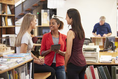 Drei weibliche Architekten, die zusammen im modernen Büro plaudern lizenzfreie stockfotos