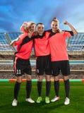 Drei weibliche Fußballspieler, die Sieg auf dem Fußball archiviert feiern stockbild
