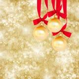 Drei Weihnachtsbälle auf goldenem Hintergrund Stockfotografie