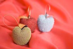 Drei Weihnachtsbaumäpfel auf rotem Hintergrund Stockfotos