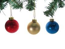 Drei Weihnachtskugelverzierungen mit den Baumzweigen getrennt. Stockfotografie