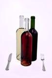 Drei Weinflaschen mit Messer und Gabel. Stockfotografie