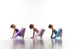 Drei wenige Ballettmädchen, die im Ballettröckchen sitzen und zusammen aufwerfen Stockfotos