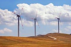 Drei Windmühlen auf Hintergrund von gelben Weiden und von blauem Himmel mit weißen Wolken Montenegro, Niksic, Krnovo Lizenzfreies Stockfoto
