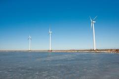 Drei Windmühlen nähern sich gefrorenem See Stockfotografie