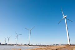 Drei Windmühlen nähern sich gefrorenem See Stockbilder