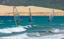 Drei Windsurfers auf sandigem Tarifa setzen in Südspanien auf den Strand Lizenzfreie Stockbilder