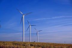 Drei Windturbinen in einer Reihe, landwirtschaftliche Landschaft. Stockbilder