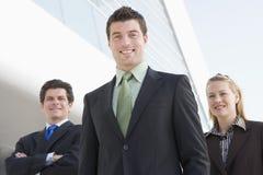 Drei Wirtschaftler, die draußen durch Gebäude stehen Stockfotografie