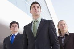 Drei Wirtschaftler, die draußen durch Gebäude stehen Stockfotos