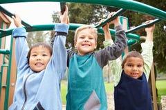 Drei Young Boys auf kletterndem Rahmen im Spielplatz Stockfotografie
