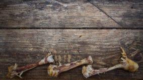 Drei zerfrassen Hühnerknochen auf einem hölzernen Brett mit einem Platz für Aufschriften lizenzfreie stockbilder
