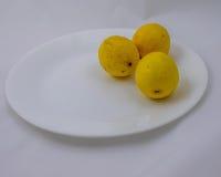 Drei Zitronen auf einer Platte Lizenzfreies Stockbild