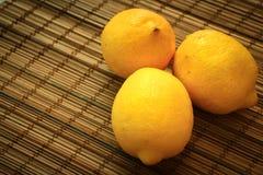 Drei Zitronen auf einer Strohbettwäsche lizenzfreies stockbild