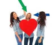 Drei zufällige Frauen, die ihr großes Herz mit Pfeilen zeigen Stockfoto