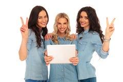 Drei zufällige Frauen mit einer Tablette, die Siegeszeichen macht Lizenzfreie Stockfotos