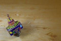 Dreidel émaux lumineux et coloré de Hanoucca en métal sur une table en bois Image libre de droits