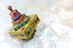 Dreidel coloré de Hanoucca de cloisonne sur le fond blanc mou, l'espace pour le texte Photographie stock