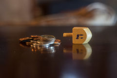Dreidel di legno accanto alla pila di monete Fotografie Stock Libere da Diritti