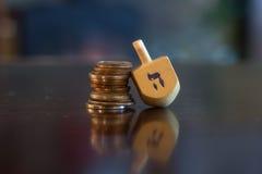 Dreidel di legno che riposa sulla pila di monete Fotografia Stock Libera da Diritti