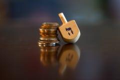 Dreidel di legno che riposa sulla pila di monete Immagine Stock Libera da Diritti