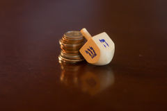 Dreidel di legno che riposa sulla pila di monete Fotografie Stock Libere da Diritti