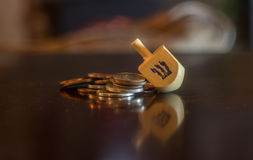 Dreidel en bois se reposant sur la pile des pièces de monnaie Images libres de droits