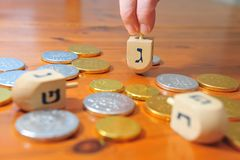 Dreidels and Gelt. Photo of someone spinning a spinning top (dreidel) and candy coins (gelt) for Hanukkah