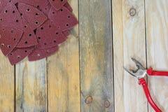 Dreieck-Schleifpapiere auf hölzernen Brettern mit Zangen diagonal lizenzfreies stockbild