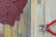 Dreieck-Schleifpapiere auf hölzernen Brettern mit Zangen horizontal lizenzfreies stockbild