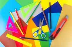 Dreiecke, Machthaber, Scheren, Bleistifte und Schneider auf farbigem Papier Stockfoto