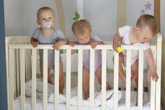 Dreiergruppen in der Krippe, in den Jungen des Dreiergruppenbabys zwei und in einem Mädchen - zusammen lizenzfreies stockbild