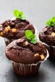Dreifache Schokoladenmuffins auf schwarzem Steinhintergrund Stockbilder