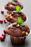 Dreifache Schokoladenmuffins mit Moosbeeren auf schwarzem Stein-backgr Stockbilder