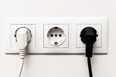 Dreifacher elektrischer Sockel mit zwei verstopften Kabeln Stockfoto