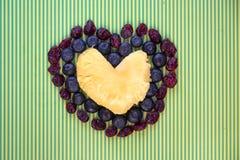 Dreifaches Herz gemacht von der Ananas, von den frischen Blaubeeren und von getrockneten Moosbeeren lizenzfreies stockfoto