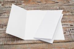 Dreifachgefaltetes weißes Schablonenpapier auf hölzerner Beschaffenheit lizenzfreie stockbilder