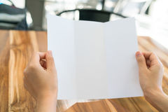 Dreifachgefaltetes weißes Schablonenpapier des Frauenhandgriffs auf hölzerner Beschaffenheit stockbild
