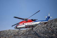 Dreifarbiger Rettungshubschrauber in Rotem, in weißem und Blau kommt unten für die Landung lizenzfreie stockfotos