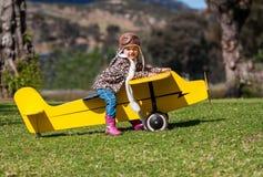 Dreijähriges Mädchen auf gelbem Spielzeugflugzeug draußen stockfotografie