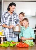 Dreiköpfige Familie, die Gemüse kocht Stockfotos