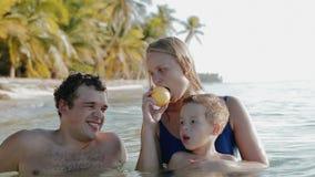 Dreiköpfige Familie, die im Meerwasser in den Tropen sich entspannt stock footage