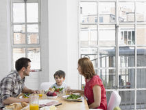 Dreiköpfige Familie, die Mahlzeit an Speisetische hat Stockfoto