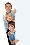 Dreiköpfige Familie hinter leerem whiteboard Lizenzfreies Stockfoto