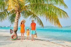 Dreik?pfige Familie auf Strand unter Palme lizenzfreies stockbild