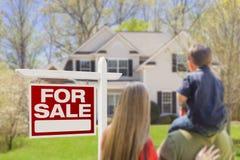 Dreiköpfige Familie, die für Verkaufs-Real Estate-Zeichen und -haus gegenüberstellt Stockbilder