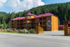 Dreistöckiger Hotelkomplex von einem Holzrahmen auf einem Hintergrund von grünen Fichten stockbilder