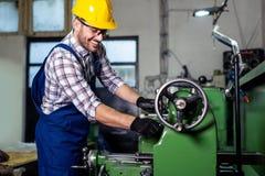 Drejarearbetaren arbetar p? en drejb?nkmaskin i en fabrik arkivfoto