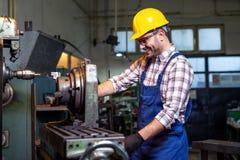 Drejarearbetaren arbetar p? en drejb?nkmaskin i en fabrik royaltyfria foton